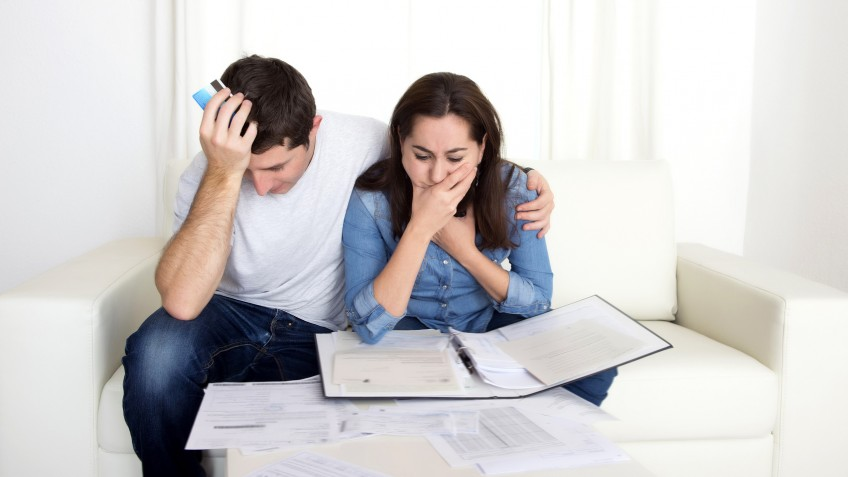 young couple worried at home in stress accounting bank documents