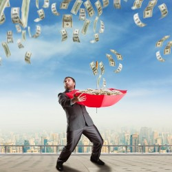 Businessman with umbrella full of money and money are falling