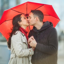 Couple in love under red umbrella.