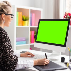 Designer using graphics tablet while working with computer