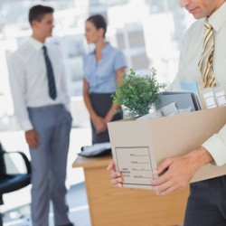 Businessman leaving office after being laid off carrying box of his things