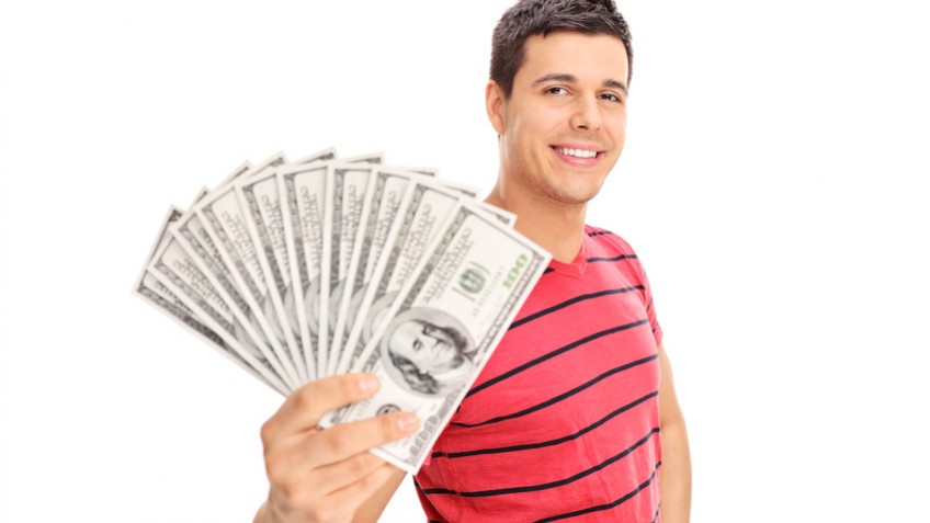Happy young man holding a pile of cash