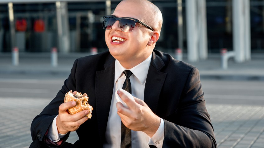 Businessman or banker working with laptop and having snack with burger outside the airport or contemporary building