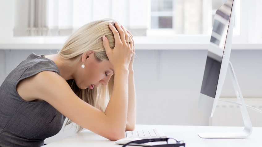 Overworked and tired young woman in front of computer