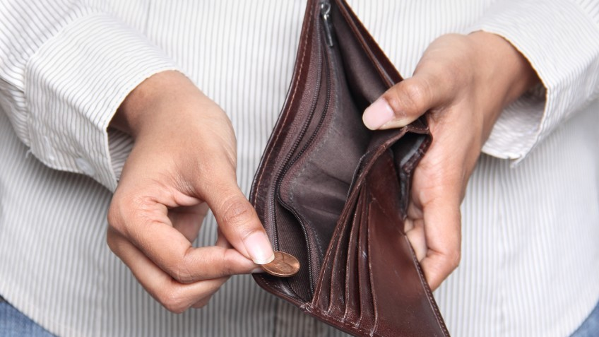 Business person taking a penny from a wallet
