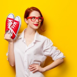 Beautiful redhead girl in white shirt with gumshoes on yellow background.