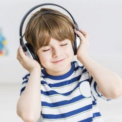 Cute boy wearing headphones and enjoying music