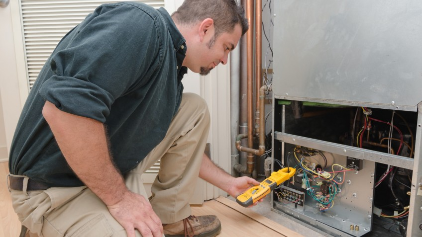 HVAC technician using a meter to check heat pump amperage