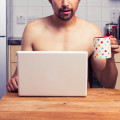 Naked man at home with laptop and coffee