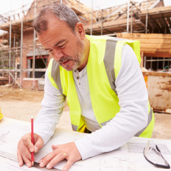 Construction Worker Looking At Plans On Building Site