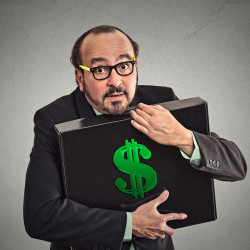 Money greed. Business man holding holding case with dollars tightly isolated on grey wall background. Worship, miser, excessive gain, finance concept