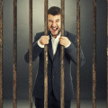 angry screaming businessman behind the prison cell over dark background