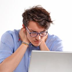 Hombre joven preocupado trabajando en un ordenador porttil.