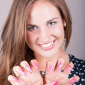Beautiful woman shows her pink gel nails with flowers, focus on nails