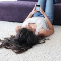 woman lying on the floor who is using the smart phone