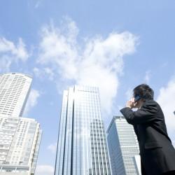 電話をしながら空を見上げるビジネスマン