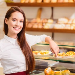 Proud of what we have created. Beautiful young female baker standing by the windowsill of her bakery and pointing at a variety of desserts and rows of fresh baked bread