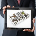 interior design concept: businessman with a tablet with interior design app on the screen