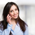 Portrait of a young smiling woman talking on the mobile phone