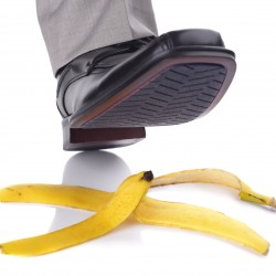 Businessman foot about to slip and fall on a banana skin