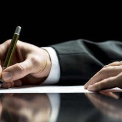 Businessman writing a letter, notes or correspondence or signing a document or agreement, close up view of his hand and the paper