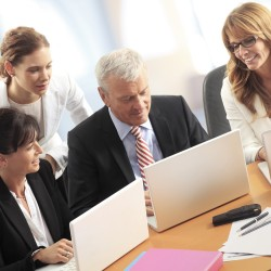 Portait of businesswomen and businessman sitting at office desk in front of computer and working together on presentation.