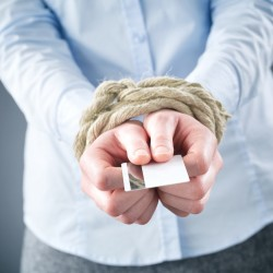 A debt concept or metaphor - a businesswoman with tied up hands holding a credit card.