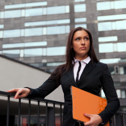 Beautiful business woman with catalog at modern building background