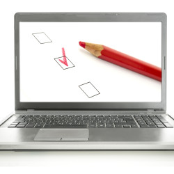 Laptop with red pencil and check boxes on screen. Online survey concept.