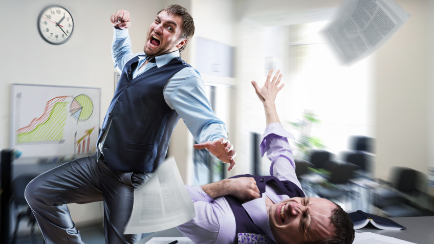 Two agressive businessmen fighting in the office