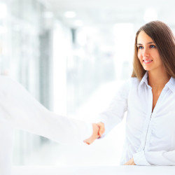 Cheerful businesspeople, or businesswoman and client handshaking